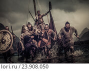 Купить «Mad vikings warriors in attack, running along shore with Drakkar on background.», фото № 23908050, снято 29 августа 2016 г. (c) Andrejs Pidjass / Фотобанк Лори