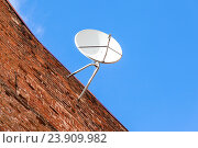 Купить «Спутниковая тарелка установлена на старой кирпичной стене на фоне голубого неба», фото № 23909982, снято 23 апреля 2018 г. (c) FotograFF / Фотобанк Лори