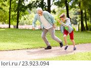 Купить «grandfather and grandson racing at summer park», фото № 23923094, снято 9 июля 2016 г. (c) Syda Productions / Фотобанк Лори
