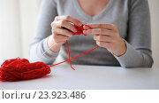 Купить «woman knitting with needles and red yarn», видеоролик № 23923486, снято 22 октября 2016 г. (c) Syda Productions / Фотобанк Лори