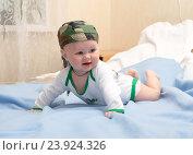 Купить «Малыш в камуфлированной бандане играет лежа на животе», фото № 23924326, снято 23 мая 2015 г. (c) Андрей Некрасов / Фотобанк Лори
