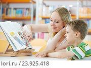 Купить «young woman and boy reading book in library», фото № 23925418, снято 19 июня 2013 г. (c) Дмитрий Калиновский / Фотобанк Лори