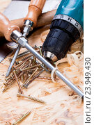 Купить «Battery-operated portable hand drill with timber, screwdrivers and screws surrounded by fresh wood shavings in a carpentry, joinery, DIY or construction concept», фото № 23949430, снято 26 марта 2014 г. (c) easy Fotostock / Фотобанк Лори