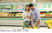 Купить «couple with food in shopping cart at grocery store», видеоролик № 23957170, снято 24 октября 2016 г. (c) Syda Productions / Фотобанк Лори