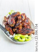 Купить «Куриные крылышки на тарелке с зеленым перцем», фото № 23996154, снято 15 мая 2016 г. (c) Марина Сапрунова / Фотобанк Лори