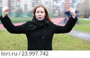 Девушка стоит на стадионе и показывает силу руками. Стоковое видео, видеограф Кекяляйнен Андрей / Фотобанк Лори