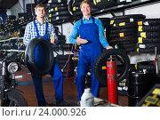 Купить «Mechanics working with new tires», фото № 24000926, снято 26 сентября 2018 г. (c) Яков Филимонов / Фотобанк Лори