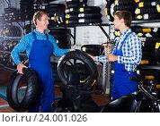 Купить «Mechanics working with new tires», фото № 24001026, снято 26 сентября 2018 г. (c) Яков Филимонов / Фотобанк Лори