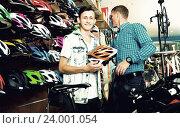 Купить «Man with teenager son buying protective helmet», фото № 24001054, снято 27 сентября 2016 г. (c) Яков Филимонов / Фотобанк Лори