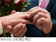 Купить «Молодой человек надевает золотое обручальное кольцо на палец невесте», эксклюзивное фото № 24082962, снято 15 октября 2016 г. (c) Игорь Низов / Фотобанк Лори