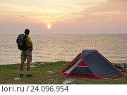 Мужчина стоит у туристической палатки на берегу моря. Стоковое фото, фотограф Станислав Толстнев / Фотобанк Лори