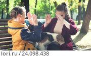 Купить «Две сестры играют в парке сидя на скамейке», видеоролик № 24098438, снято 27 октября 2016 г. (c) Сергей Мнацаканов / Фотобанк Лори