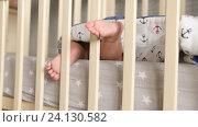 Купить «Little bare heels between railings of a cradle. Baby moving feet. Handheld shot», видеоролик № 24130582, снято 9 октября 2016 г. (c) Павел Котельников / Фотобанк Лори