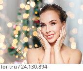 Купить «woman touching her face over christmas lights», фото № 24130894, снято 14 апреля 2016 г. (c) Syda Productions / Фотобанк Лори