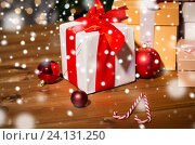 Купить «gifts, candies and christmas balls on wooden board», фото № 24131250, снято 1 октября 2015 г. (c) Syda Productions / Фотобанк Лори