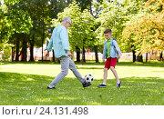 Купить «old man and boy playing football at summer park», фото № 24131498, снято 9 июля 2016 г. (c) Syda Productions / Фотобанк Лори