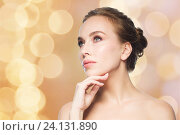 Купить «beautiful woman touching her face over lights», фото № 24131890, снято 14 апреля 2016 г. (c) Syda Productions / Фотобанк Лори