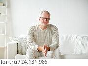 Купить «smiling senior man in glasses sitting on sofa», фото № 24131986, снято 7 июля 2016 г. (c) Syda Productions / Фотобанк Лори