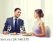 Купить «smiling couple eating main course at restaurant», фото № 24144570, снято 9 марта 2014 г. (c) Syda Productions / Фотобанк Лори