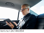 Купить «senior businessman with tablet pc driving in car», фото № 24144854, снято 16 июля 2016 г. (c) Syda Productions / Фотобанк Лори