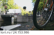 Купить «Колесо велосипеда на фоне канала в Амстердаме», видеоролик № 24153986, снято 4 апреля 2020 г. (c) Константин Шишкин / Фотобанк Лори