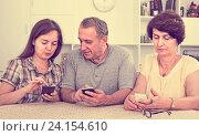 Купить «senior parents and daughter with smartphones», фото № 24154610, снято 13 ноября 2019 г. (c) Яков Филимонов / Фотобанк Лори
