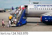 Купить «Пассажиры спускаются по трапу, выходя из самолета», фото № 24163970, снято 28 июня 2016 г. (c) Дмитрий УТКИН / Фотобанк Лори