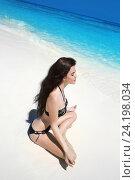 Купить «Красивая молодая девушка в черном бикини сидит в позе лотоса на тропическом пляже», фото № 24198034, снято 16 февраля 2016 г. (c) Photobeauty / Фотобанк Лори