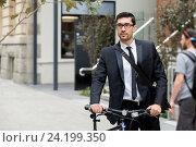 Купить «Young businessmen with a bike», фото № 24199350, снято 4 апреля 2015 г. (c) Sergey Nivens / Фотобанк Лори