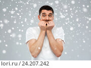 Купить «scared man in white t-shirt over snow background», фото № 24207242, снято 15 января 2016 г. (c) Syda Productions / Фотобанк Лори