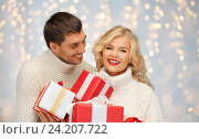 Купить «smiling man and woman with presents over lights», фото № 24207722, снято 7 октября 2012 г. (c) Syda Productions / Фотобанк Лори