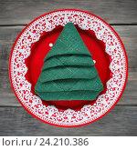 Купить «Салфетка сложенная в форме рождественской елки в красной тарелке, вид сверху. Праздничная сервировка», фото № 24210386, снято 6 ноября 2016 г. (c) Сергей Чайко / Фотобанк Лори
