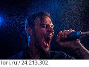 Молодой эмоциональный мужчина громко поет в микрофон в сценическом свете. Стоковое фото, фотограф Pavel Biryukov / Фотобанк Лори