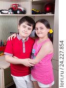 Купить «Брат и сестра стоят стоят обнявшись в детской комнате», фото № 24227854, снято 23 августа 2016 г. (c) Emelinna / Фотобанк Лори