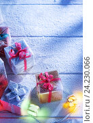 Купить «Close up view  of gifts boxes  on snowbound  wooden back», фото № 24230066, снято 27 октября 2016 г. (c) Дмитрий Эрслер / Фотобанк Лори