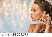 close up of woman woman fastening diamond earring. Стоковое фото, фотограф Syda Productions / Фотобанк Лори