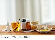 Купить «drugs, thermometer, honey and cup of tea on wood», фото № 24235862, снято 13 октября 2016 г. (c) Syda Productions / Фотобанк Лори