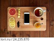 Купить «smartphone with cup of lemon tea, honey and ginger», фото № 24235870, снято 13 октября 2016 г. (c) Syda Productions / Фотобанк Лори