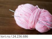 Купить «knitting needles and ball of pink yarn on wood», фото № 24236686, снято 20 октября 2016 г. (c) Syda Productions / Фотобанк Лори