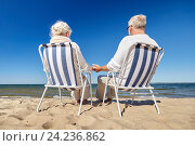 Купить «senior couple sitting on chairs at summer beach», фото № 24236862, снято 18 августа 2015 г. (c) Syda Productions / Фотобанк Лори