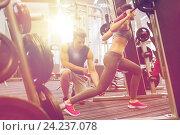 Купить «man and woman with barbell flexing muscles in gym», фото № 24237078, снято 30 ноября 2014 г. (c) Syda Productions / Фотобанк Лори
