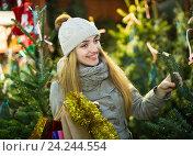 Купить «Young cheerful woman buying Xmas tree at festive fair», фото № 24244554, снято 27 января 2020 г. (c) Яков Филимонов / Фотобанк Лори