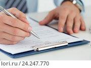 Мужчина заполняет ручкой документ. Стоковое фото, фотограф Людмила Дутко / Фотобанк Лори