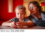 Купить «Девочка смотрит в телефон», фото № 24248094, снято 11 октября 2014 г. (c) Хайрятдинов Ринат / Фотобанк Лори