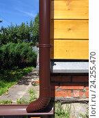 Купить «Коричневая водосточная труба на углу деревянного дома», фото № 24255470, снято 29 июня 2016 г. (c) Анатолий Заводсков / Фотобанк Лори