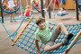 Десятилетний мальчик качается в гамаке на детской площадке, фото № 24258862, снято 30 июля 2016 г. (c) Юлия Кузнецова / Фотобанк Лори