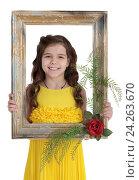 Купить «Улыбающаяся девочка в желтом платье держит перед собой картинную рамку», фото № 24263670, снято 20 марта 2016 г. (c) Игорь Долгов / Фотобанк Лори