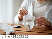 Купить «woman stirring medication in cup with spoon», фото № 24265802, снято 13 октября 2016 г. (c) Syda Productions / Фотобанк Лори