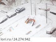 Купить «Занесенный снегом двор жилого дома с детской площадкой и припаркованными автомобилями», фото № 24274942, снято 13 ноября 2016 г. (c) Кекяляйнен Андрей / Фотобанк Лори