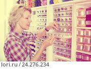 Купить «Female next to shelf with buttons», фото № 24276234, снято 23 мая 2019 г. (c) Яков Филимонов / Фотобанк Лори